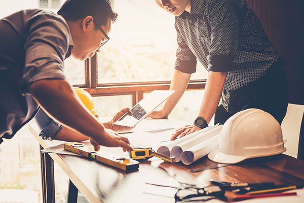 a construction manager and a general contractor looking at a construction blueprint
